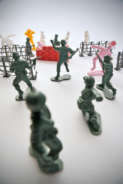 Some green toy soldiers fighting a mock up battle